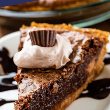 slice of chocolate pie with graham crust on white plate with hot fudge