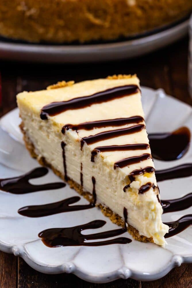 One slice of classic cheesecake on a scalloped plate with a chocolate sauce drizzle