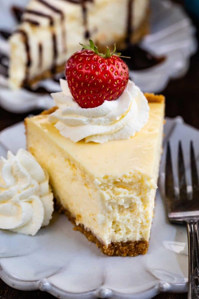 Slice of classic cheesecake with whipped cream and strawberry on top with one bite missing