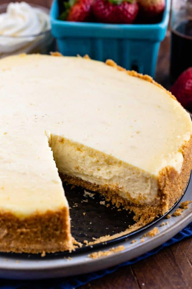 Overhead shot of classic cheesecake with one slice missing