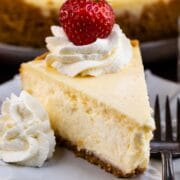 A slice of classic cheesecake on a plate with whipped cream and a strawberry on top