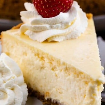 A slice of classic cheesecake on a plate with whipped cream and a strawberry on top and recipe title on top of image