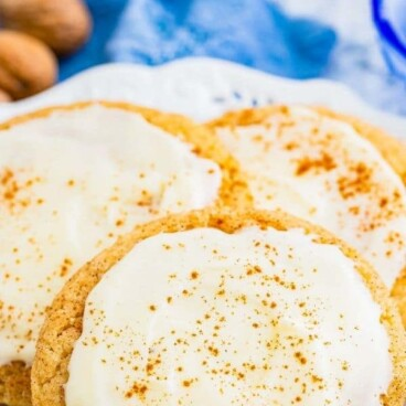 Eggnog snickerdoodles with eggnog frosting on a plate and recipe title on top of photo