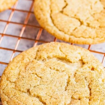 Eggnog snickerdoodle cookies on a metal cooling rack with recipe title on top of photo