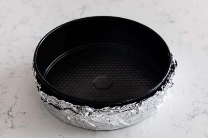 Overhead shot of springform cheesecake pan with foil on the outside