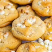 White chocolate macadamia nut cookies with white chocolate chips around
