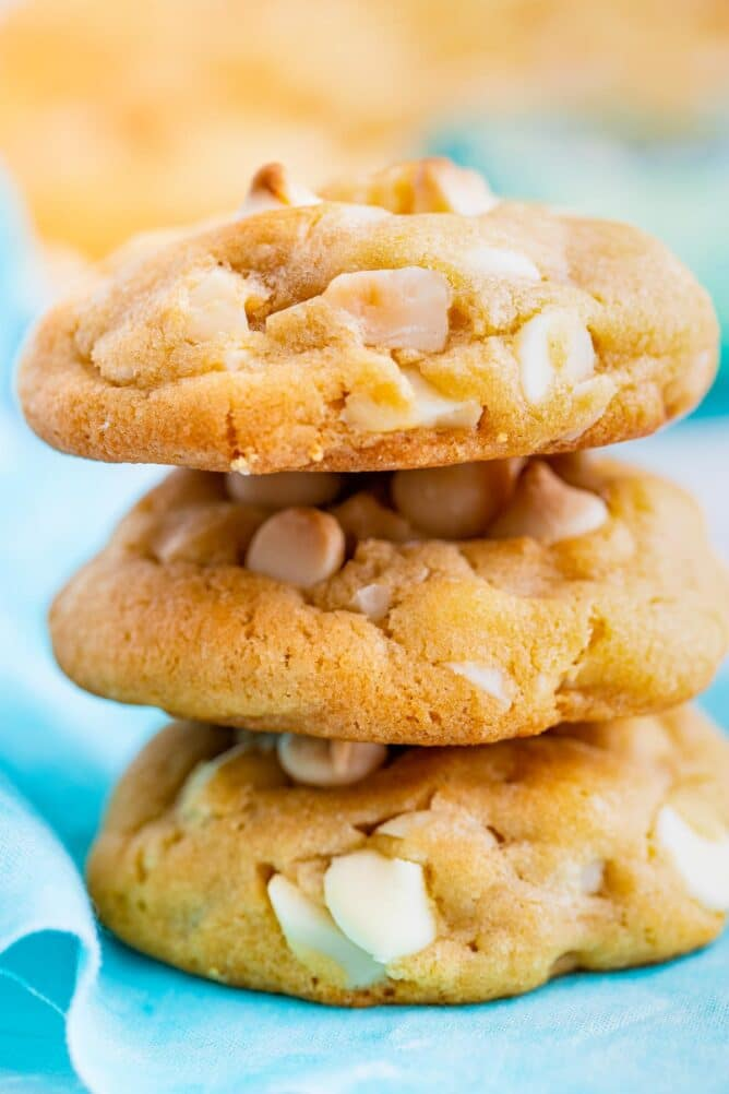 Side shot of white chocolate macadamia nut cookies stacked on top of eachother