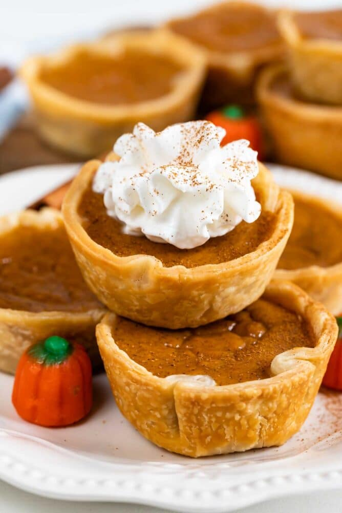 Close up photo of mini pumpkin pies stacked on top of eachother and the top one has whipped cream