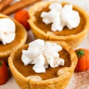 Three mini pumpkin pies with whipped cream on top