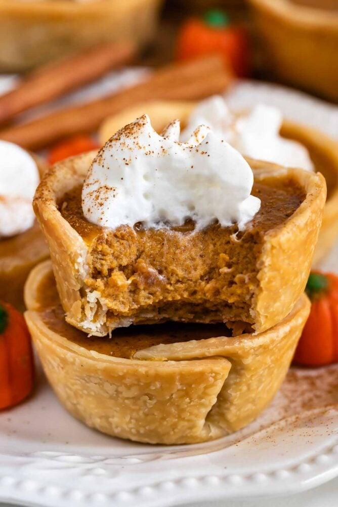 Close up of a mini pumpkin pie with whipped cream cut in half to show pumpkin filling
