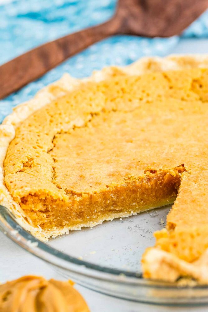 Peanut butter chess pie in glass pie dish with one slice missing