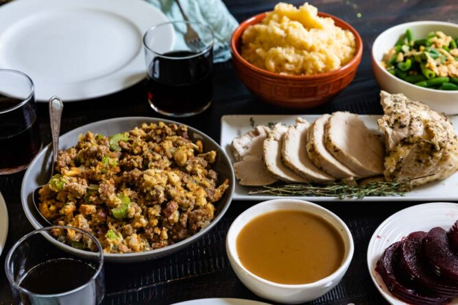 table with place settings and sausage stuffing, sliced turkey breast, bowl of gravy, cranberry sauce, orange bowl of mashed potatoes and bowl of green beans with glasses of coke