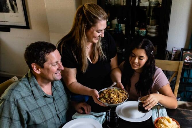 Family at dinner table with mom serving stuffing
