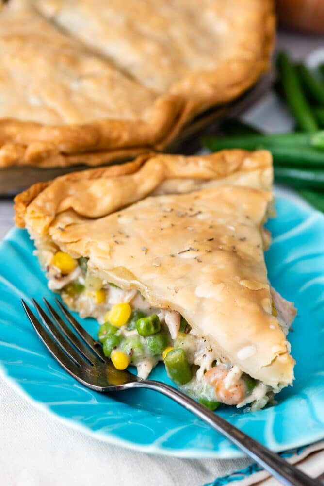 Close up shot of slice of turkey pot pie on a turquoise plate