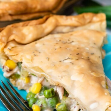 Close up shot of slice of turkey pot pie on a turquoise plate with recipe title on top of image
