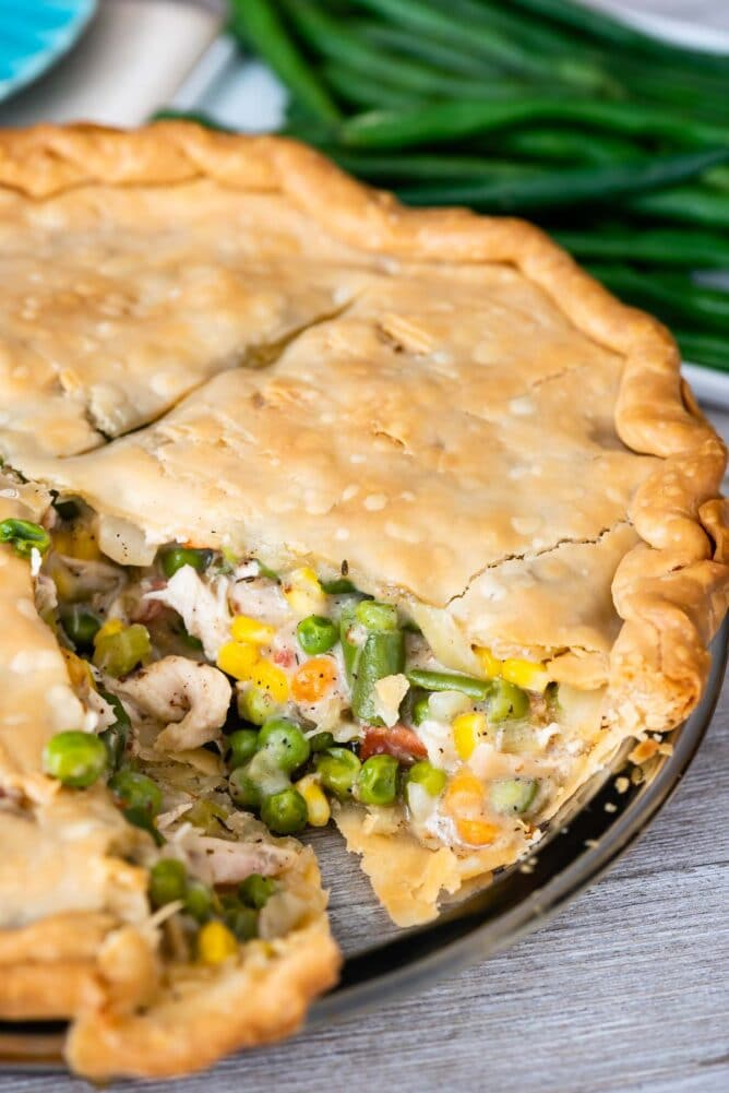 Turkey pot pie in a glass pie dish with one slice missing