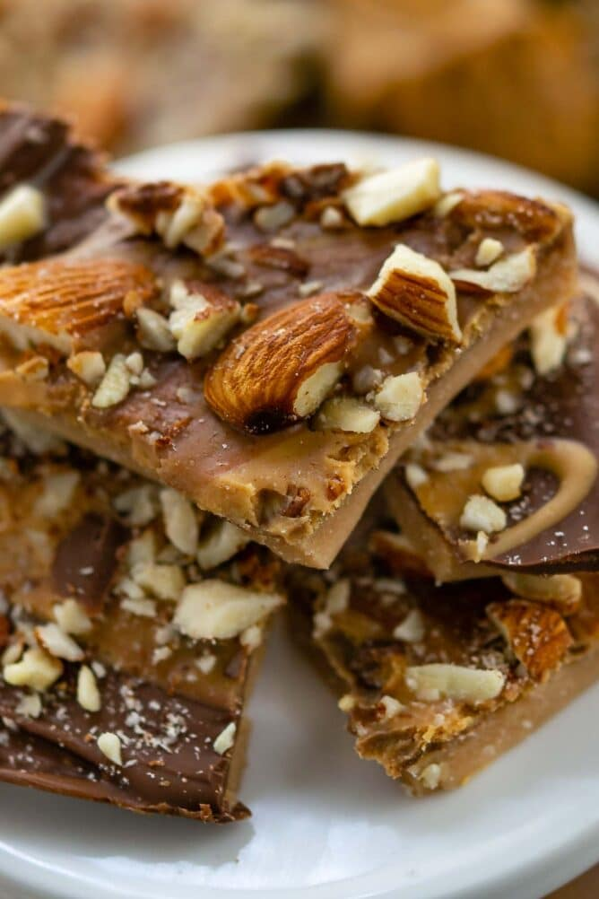Close up of toffee pieces stacked on a white serving plate