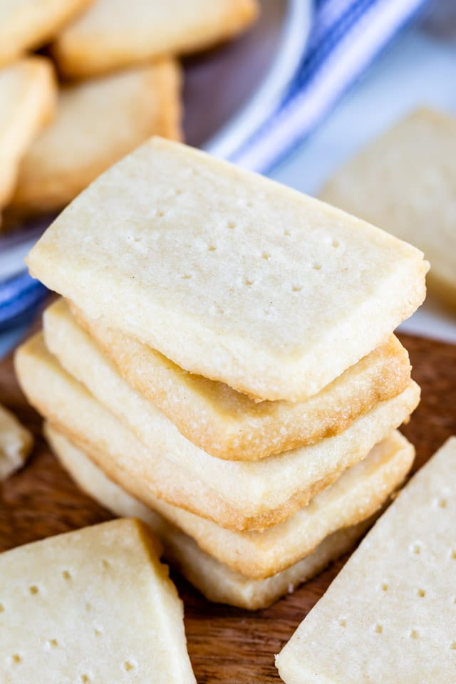 Stack of rectangular shortbread cookies on a wood cutting board