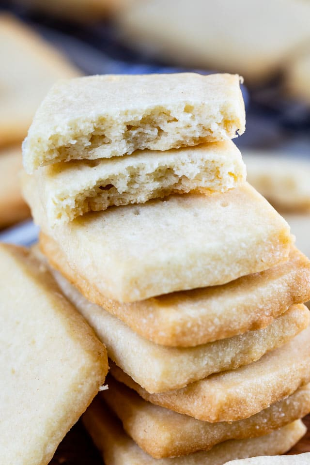 Close up shot of rectangular shortbread cookies stacked on eachother with top one broken in half