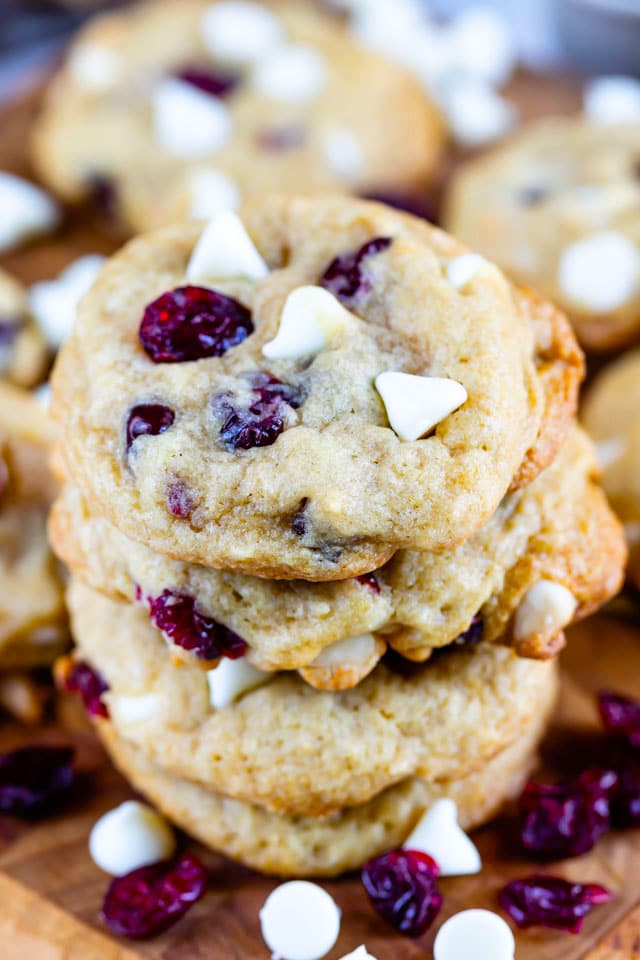 Close up shot of stacked cranberry white chocolate cookies on a wood cutting board