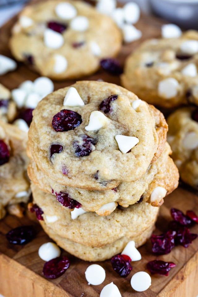 Stack of cranberry white chocolate cookies on a wood cutting board surrounded by cranberries and white chocolate chips