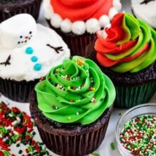 4 cupcakes decorated for christmas: snowman, Santa, swirled frosting, tree with words on photo
