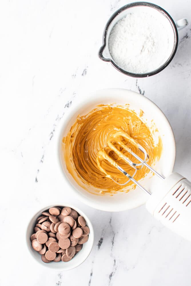Overhead view of peanut butter mixture being mixed with chocolate and powdered sugar next to it