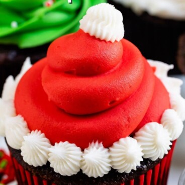 christmas cupcake decorated like a Santa hat with red frosting and white puffs