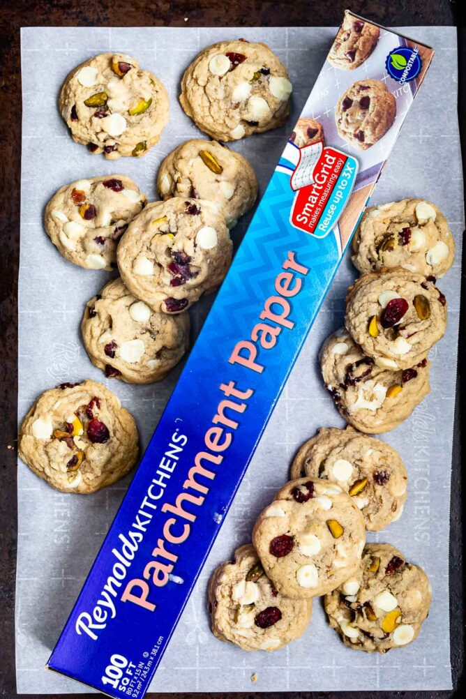 overhead shot of parchment paper on cookie sheet surrounded by cookies