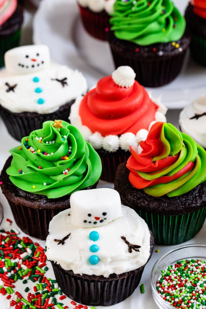 4 cupcakes decorated for christmas: snowman, Santa, swirled frosting, tree