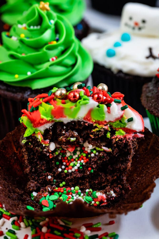 chocolate cupcake sliced open with sprinkles inside and swirled frosting