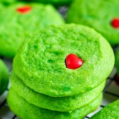 Stacks of green grinch cookies on a metal wire rack