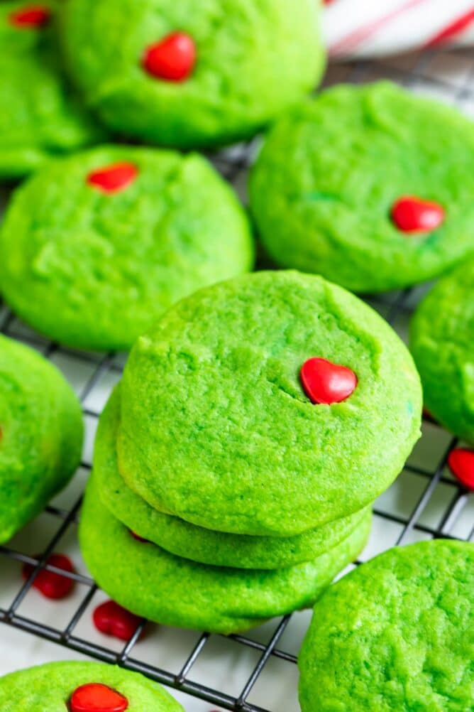 Grinch cookies stacked on a metal wire rack after cooling