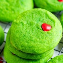 Grinch cookies stacked on a metal wire rack after cooling with recipe title on top of image