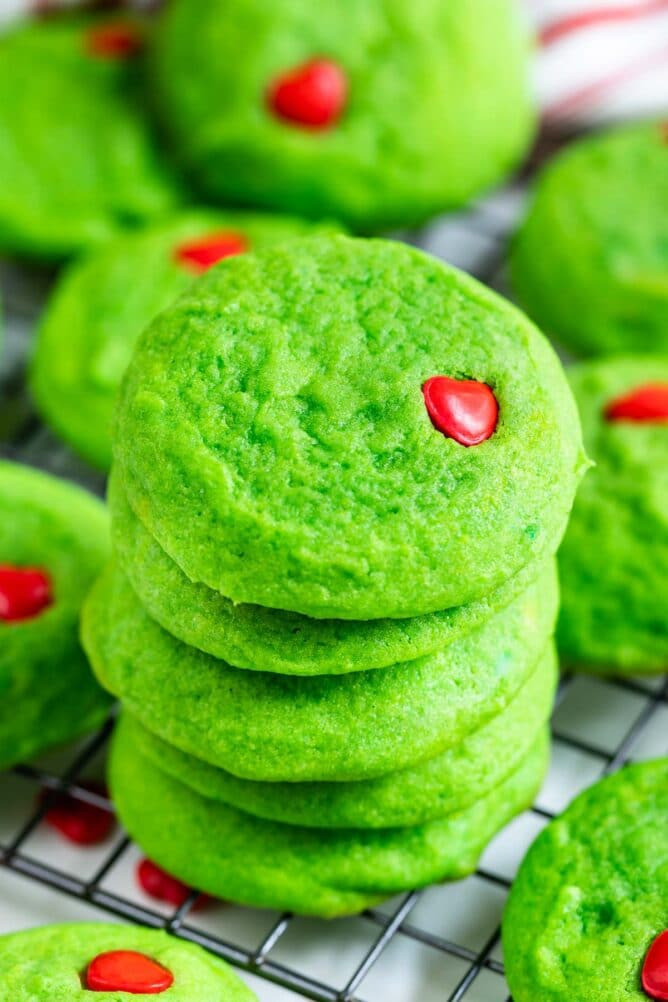 Close up photo of large stack of grinch cookies on a metal cooling rack