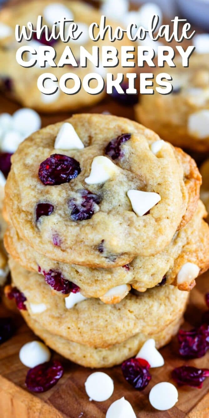 Close up shot of stacked cranberry white chocolate cookies on a wood cutting board with recipe title on top of image