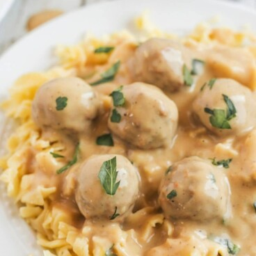 Plate full of swedish meatballs over egg noodles with recipe title on top of image