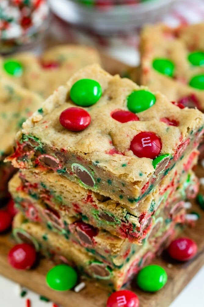 Overhead view of three christmas cookie bars stacked on eachother with m&ms all around