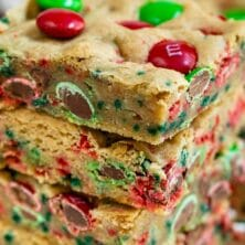 Stack of christmas cookie bars with m&ms around them and recipe title on top of image