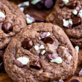 Overhead view of double chocolate mint cookies with andes mints scattered around cookies