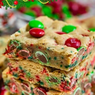 Stack of christmas cookie bars with m&ms around them with green colorblock and recipe title on top of image