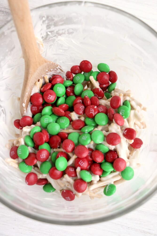 Overhead view of green and red M&Ms being stirred into ingredients in clear bowl with wooden spoon