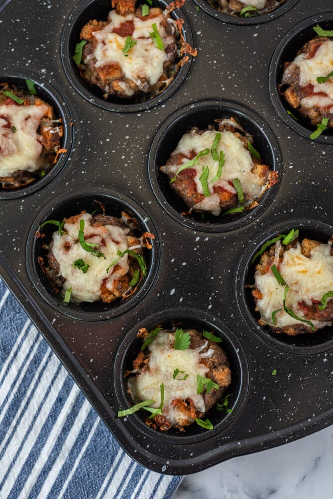 Overhead shot of baked mini meatloaves covered in cheese still in muffin tins