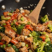 Chicken teriyaki being cooked in a wok with a wooden spoon