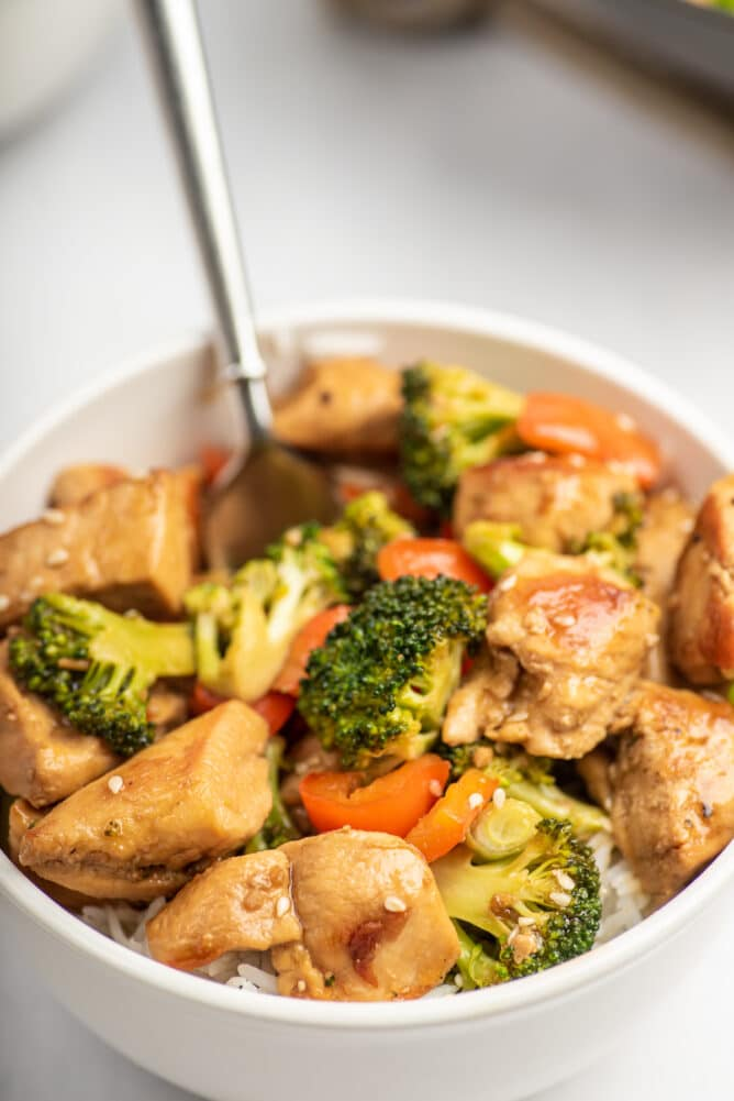 Teriyaki chicken in a white bowl with fork sticking out and recipe title on top of image