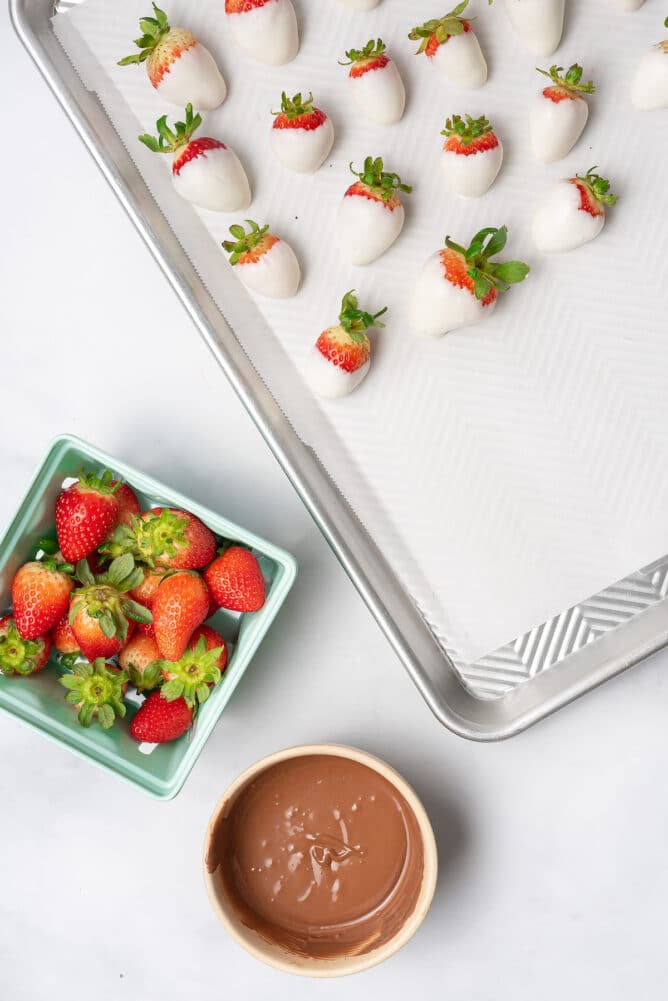 Half a sheet pan filled with white chocolate covered strawberries with more strawberries and milk chocolate on the side