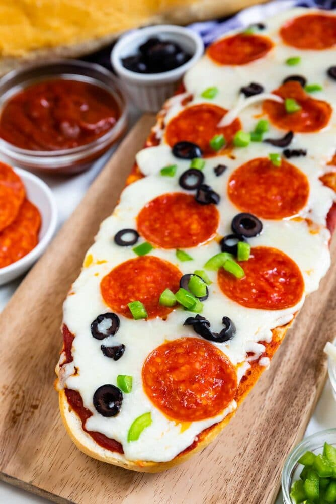 French bread pizza with pepperoni and olives on cutting board