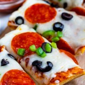 slices of French bread pizza with pepperoni and olives on cutting board