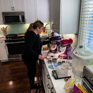 woman in kitchen with mixers and ingredients all around her