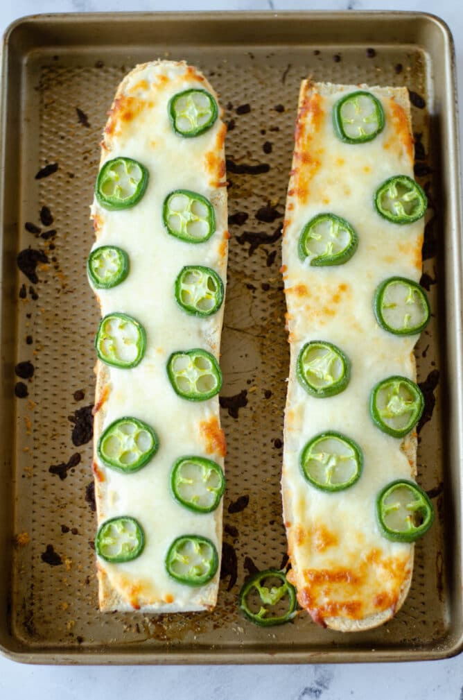 Overhead shot of two loaves of baked jalapeno cheese bread on a sheet pan